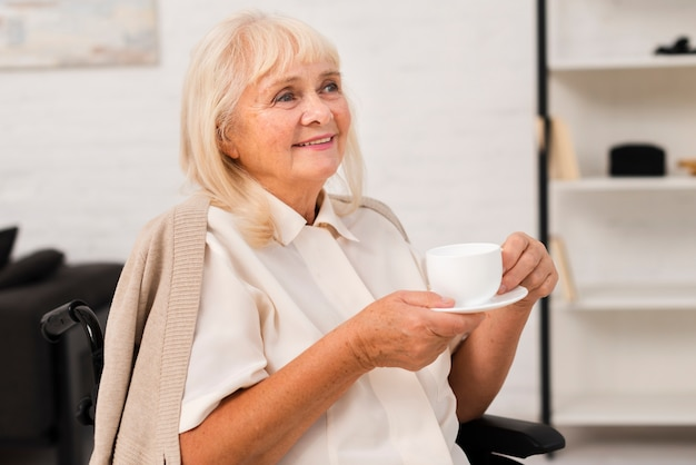 Vieille femme tenant une tasse de thé Photo gratuit