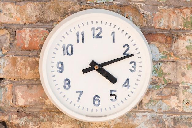 Une vieille horloge blanche contre le mur de briques Photo gratuit