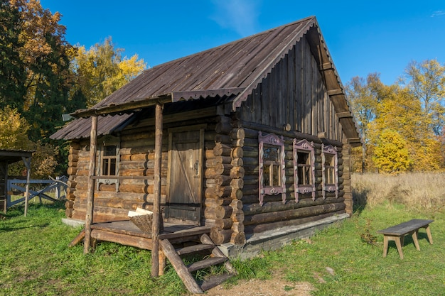 Vieille maison de rondins dans le village russe. banc dans la cour. Photo Premium