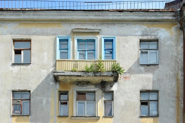 Vieille maison stalinienne typique de saint-pétersbourg de style empire avec des arbres en croissance sur le balcon Photo Premium