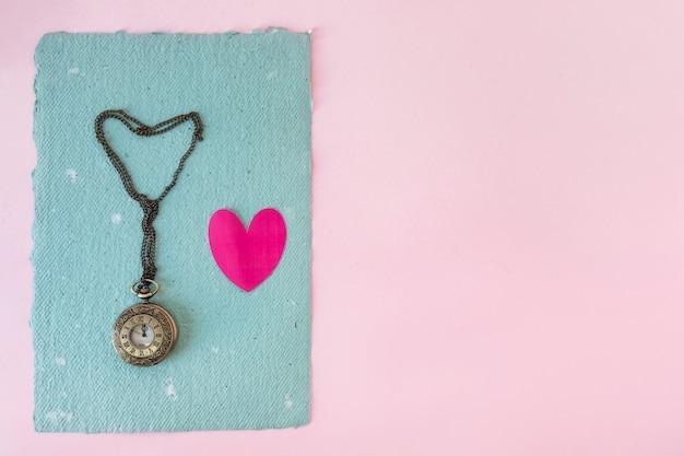 Vieille montre de poche et petit coeur sur papier bleu Photo gratuit