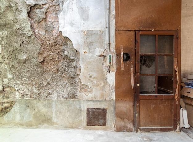 Vieille porte de chariot élévateur sur un mur cassé Photo Premium
