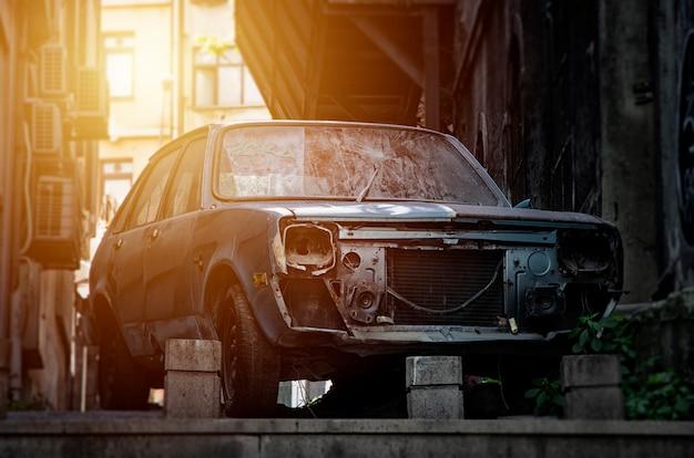 Une vieille voiture bleue cassée et rouillée abandonnée sans phares et une fissure sur le pare-brise Photo Premium