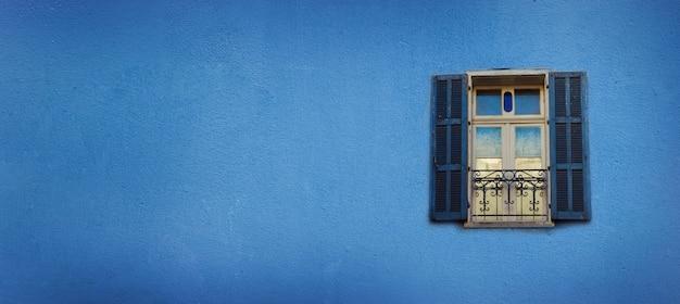 Vieilles fenêtres peintes en bleu sur le mur de béton. bannière avec espace de copie. pop art concept, fenêtre de style grec Photo Premium