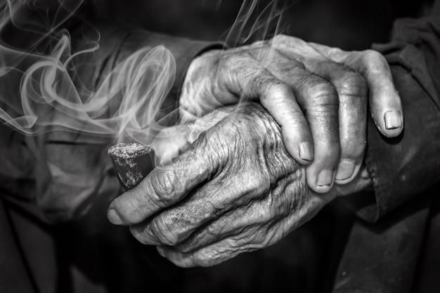 Vieilles mains tenant la pipe avec de la fumée Photo Premium