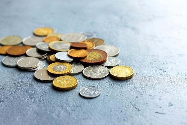 Vieilles pièces de monnaie de différents pays sur un fond de béton gris. Photo Premium