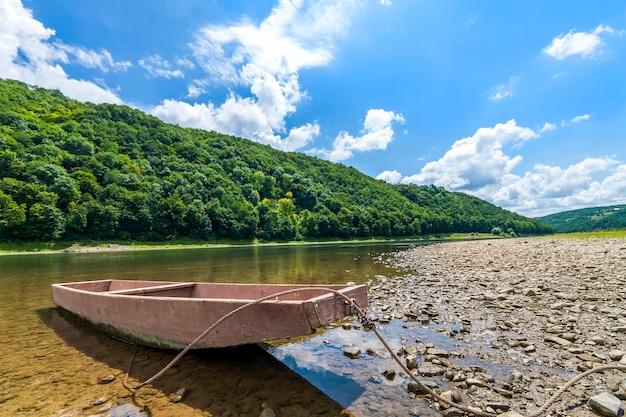Vieux bateau sur l'eau claire de la rivière avec des collines couvertes de forêts derrière Photo Premium