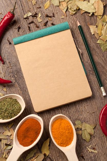 Vieux cahier, épices en cuillères Photo Premium