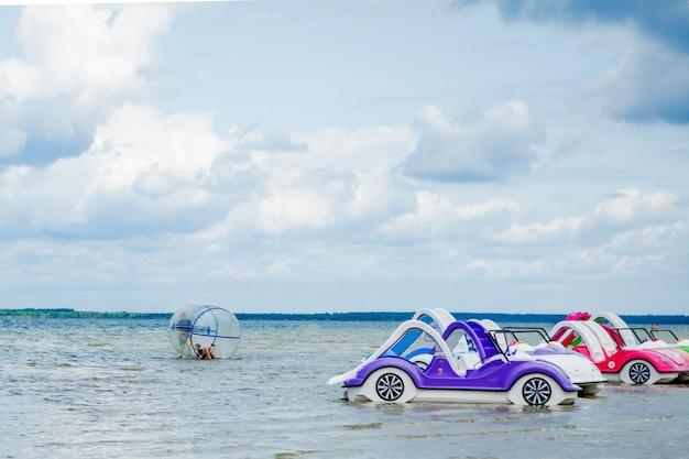 Vieux Catamarans Et Bateaux En Plastique Vintage Colorés Près D'une Jetée En Bois Sur La Rive D'un Grand Lac Photo Premium