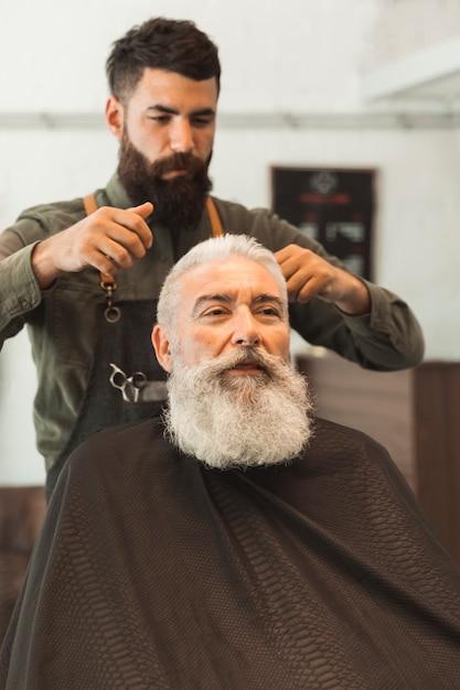 Vieux client se coupe les cheveux au salon de coiffure Photo gratuit