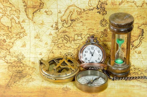 Vieux compas et sablier sur une carte du vieux monde Photo Premium