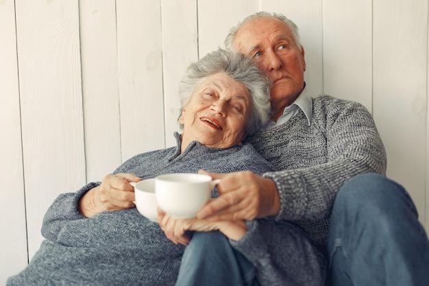 Vieux Couple élégant Assis à La Maison Sur Un Plancher Photo gratuit