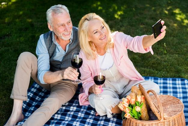 Vieux couple prenant un selfie en hauteur Photo gratuit