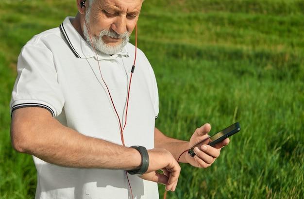 Vieux Coureur Vérifiant L'heure Pendant L'exercice à L'extérieur. Photo Premium