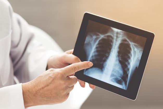 Un vieux docteur montre une image radiographique. Photo Premium