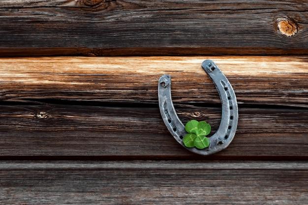 Vieux fer à cheval et trèfle à quatre feuilles sur une planche de bois vintage Photo Premium