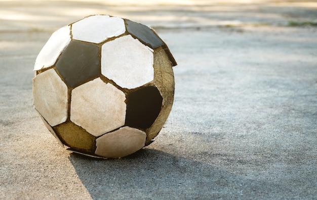 Vieux football sur le sol en béton. Photo Premium