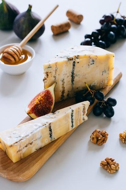 Vieux fromage anglais stilton. fromage bleu, figues et raisins sur une planche à découper en marbre Photo Premium