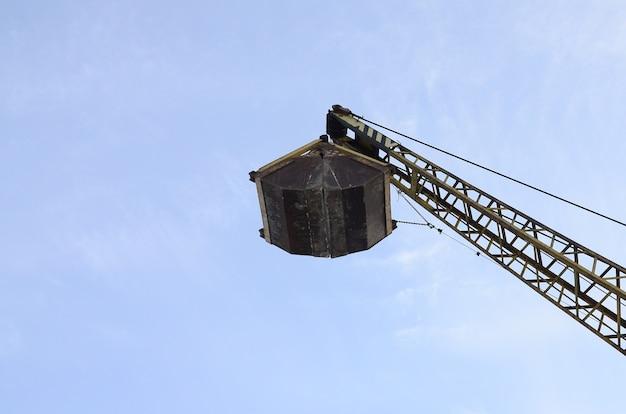 Vieux grappin mécanique jaune sur fond de ciel bleu Photo Premium