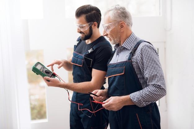 Vieux et le jeune homme font ensemble multimètre numérique. Photo Premium