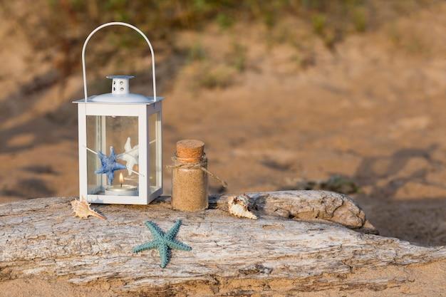 Sur le vieux journal dans une lanterne de style nautique, des coquillages, une bouteille de sable et une étoile de mer dans le sable Photo Premium