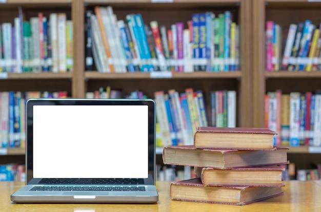 Vieux livre sur le bureau dans la bibliothèque avec tablette Photo Premium