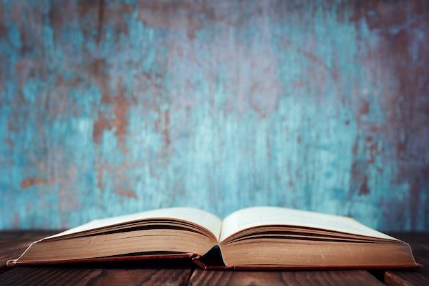 Un vieux livre ouvert sur une table en bois. le concept d'éducation Photo Premium