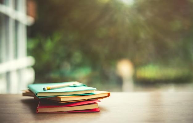 Vieux livres avec crayon sur bois table avec arrière-plan flou en soleil Photo Premium