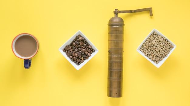 Vieux moulin à café; grains de café crus et torréfiés et tasse à café sur fond jaune vif Photo gratuit