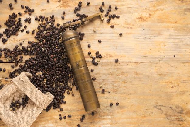 Vieux moulin à café avec grains de café tombant du sac sur la table Photo gratuit
