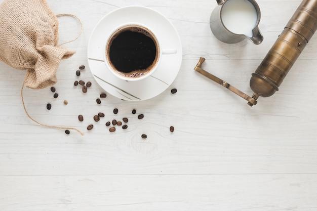 Vieux moulin à café; grains de café tombant de sac avec une tasse de café et de lait sur le bureau blanc Photo gratuit
