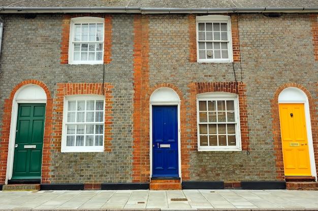 Vieux mur de briques classiques avec portes colorées en angleterre Photo Premium