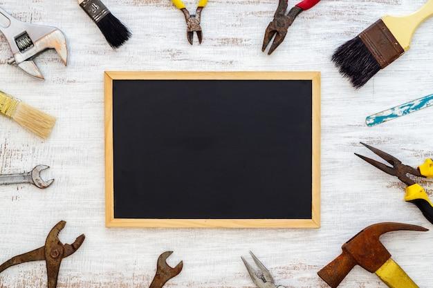 Vieux outils à main rouillés avec tableau noir Photo Premium