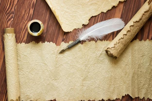 Vieux Papier, Rouleau Et Plume Sur Papier En Bois Avec Espace Copie Photo Premium