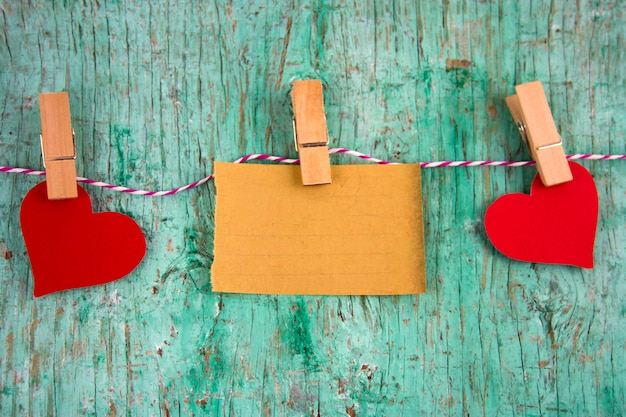 Vieux papier vierge et coeurs de papier rouges accrochés sur des pinces à linge sur une corde Photo Premium