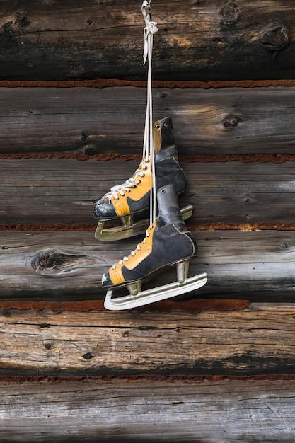 Vieux patins accroché au mur en bois Photo gratuit
