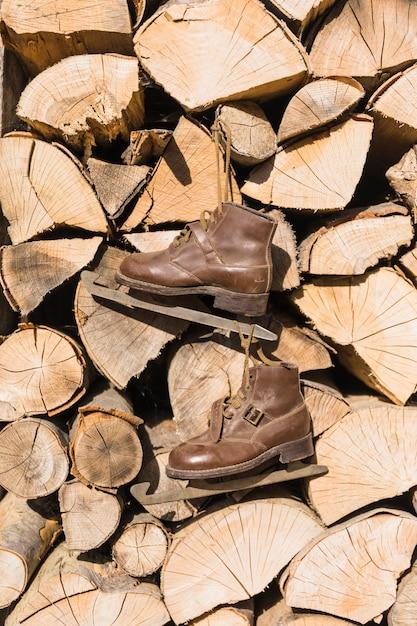 Vieux patins suspendus sur une pile de bois de chauffage Photo gratuit