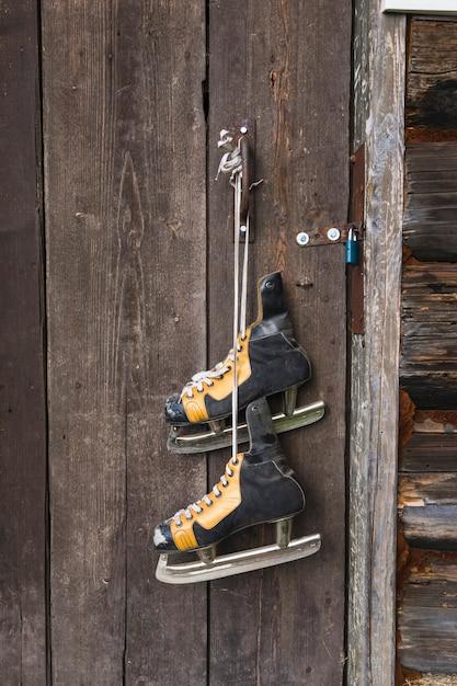 Vieux patins suspendus à une porte en bois Photo gratuit