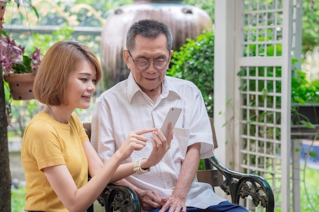 Vieux père asiatique et sa fille. une fille apprend à un père âgé à utiliser un téléphone portable Photo Premium