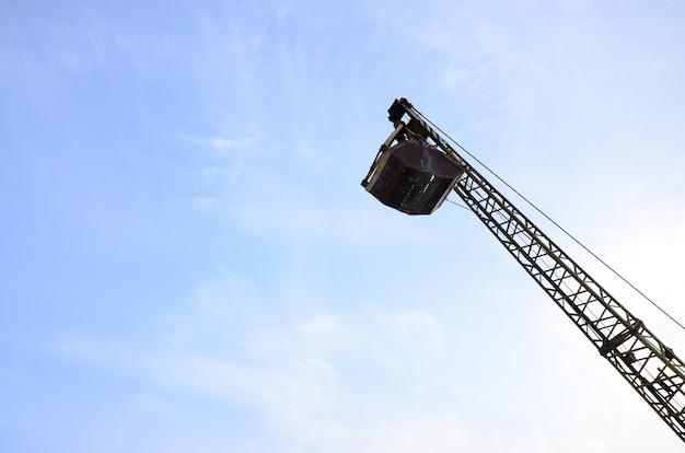 Vieux pince mécanique jaune à clapet sur ciel bleu Photo Premium