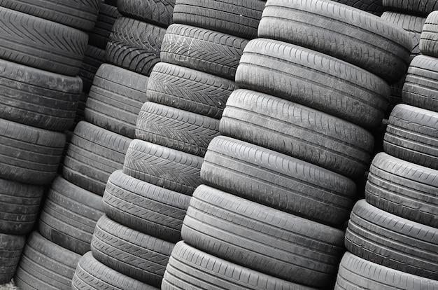 Vieux pneus usés empilés avec des pieux élevés dans le garage de l'atelier de pièces de voiture secondaire Photo Premium