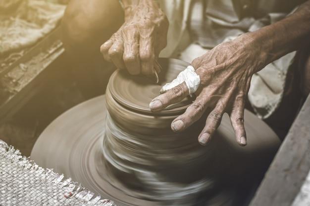 Vieux potier faisant un bol dans les travaux de poterie. vieil homme moulant de l'argile avec de l'artisanat. Photo Premium