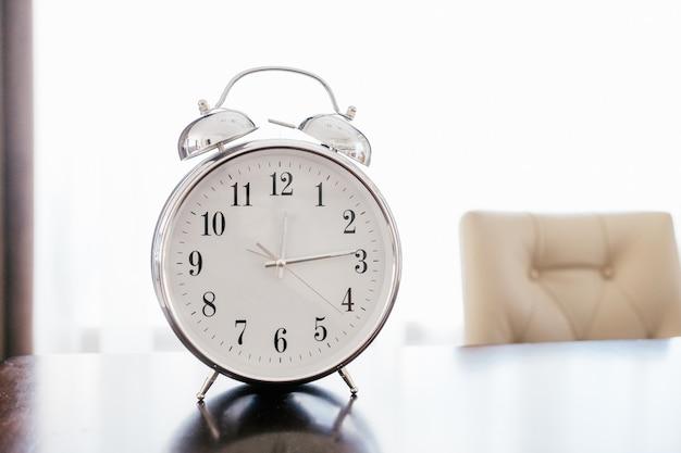 Vieux réveil rétro sur une table en bois avec fond pastel Photo Premium