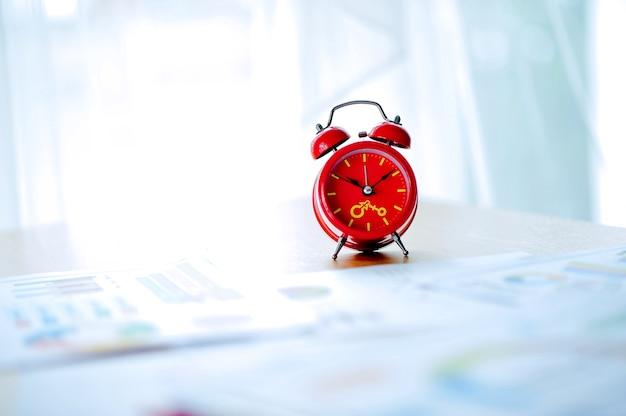 Vieux réveil rouge, réveil rouge placé dans l'espace de travail. salle blanche belles couleurs. Photo Premium