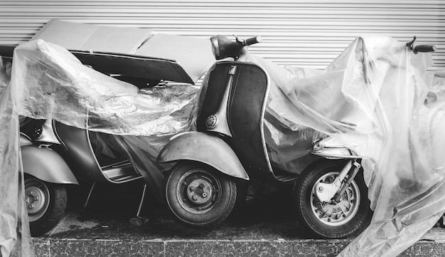Vieux scooter garé dans une rue Photo gratuit