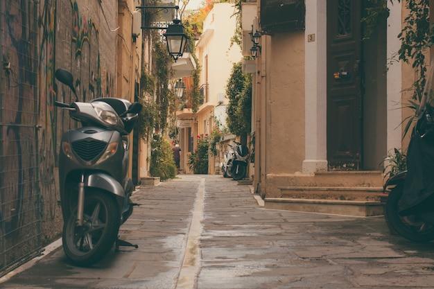Vieux scooter garé et une porte vintage de la partie de la vieille ville de rethymnon. Photo Premium