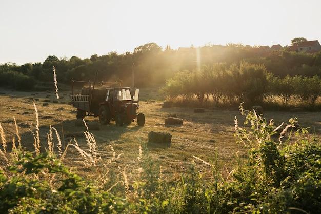 Vieux tracteur rouge ramassant les meules de foin du champ Photo gratuit