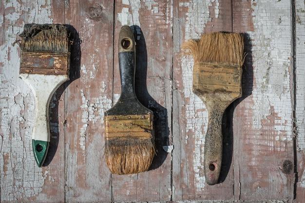 Vieux utilisé des pinceaux sur le fond d'une vieille peinture séchée. Photo Premium
