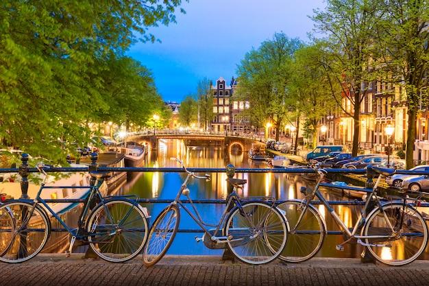 Vieux vélos sur le pont à amsterdam, pays-bas contre un canal au coucher du soleil crépuscule de l'été. Photo Premium