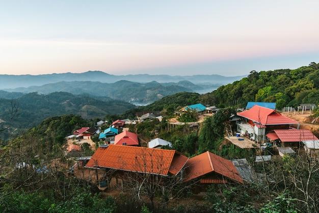 Village au milieu de couches de montagnes avec soleil et brouillard le soir Photo Premium
